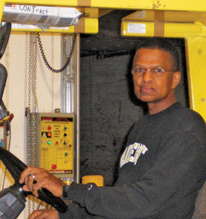 Image of Kenneth Tucker handling heavy machinery at work.